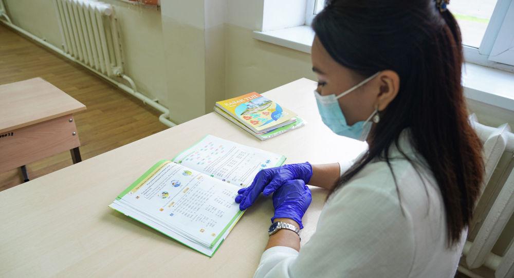 Учитель в маске и перчатках в дежурном классе