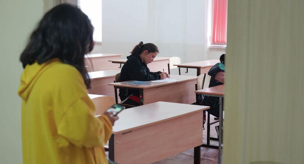 Школьница наблюдает за уроком в дежурном классе через открытую дверь
