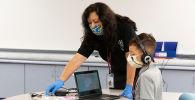 Помощник учителя с учеником в защитных масках