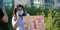 Учительница с табличкой перед школой 1 сентября