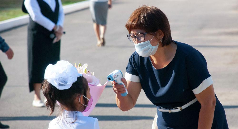 Учитель измеряет температуру первокласснице
