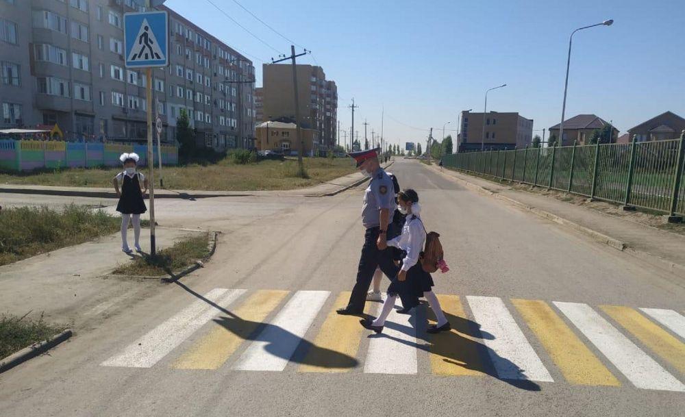 Полицейский переводит школьников через дорогу по пешеходному переходу