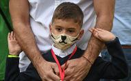Ребенок в защитной маске рядом со взрослым возле школы