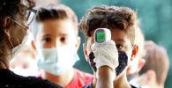 Учитель в перчатках и маске измеряет температуру у школьника перед началом занятий