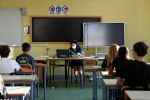 Учитель в защитной маске проводит урок в классе