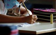 Девочка в маске пишет задание на уроке в школе
