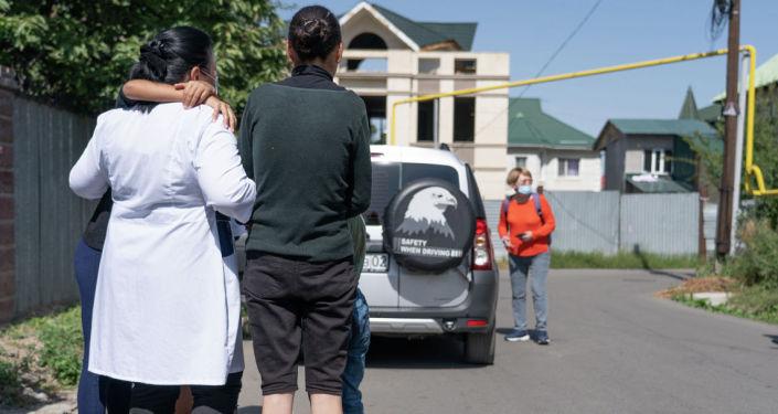 Дети и женщины прощаются с работниками приюта
