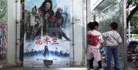 Дети возле плаката к фильму Диснея Мулан на автобусной остановке в день открытия фильма в Пекине 11 сентября 2020 год