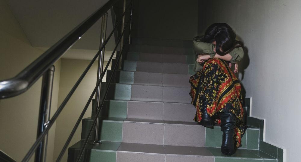 Девушка плачет на лестничной клетке, иллюстративное фото