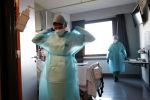 Медик поправляет защитный костюм, выходя из палаты в больнице с коронавирусом