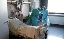 Врачи в защитных костюмах общаются с пациентом в больнице с коронавирусом