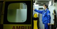 Сотрудник станции скорой помощи проверяет готовность реанимобиля к выезду