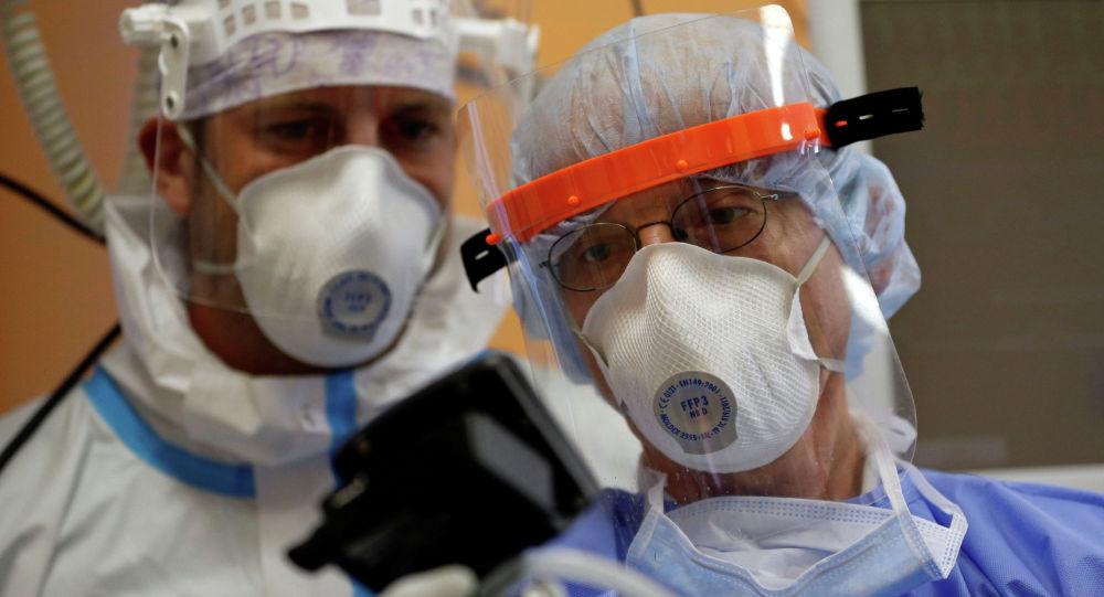 Врачи изучают показания аппаратуры в больнице с коронавирусом