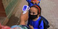 Учитель измеряет температуру школьнице