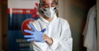 Врач в защитном костюме надевает перчатки в больнице с коронавирусом