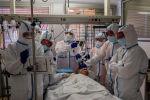 Бригада медиков следит за показаниями приборов в палате интенсивной терапии в больнице с коронавирусом