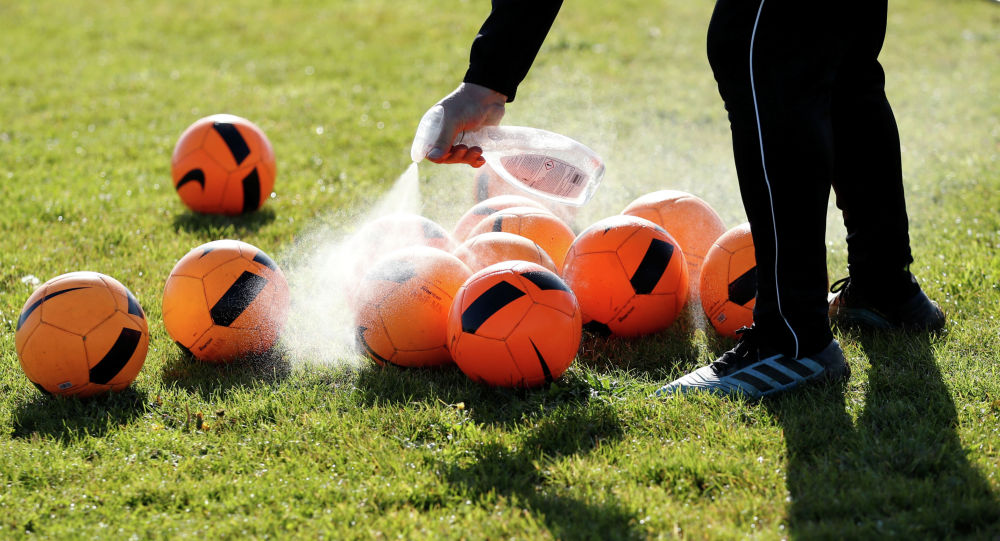 Тренер обрабатывает антисептиком  мячи на футбольном поле перед началом тренировки