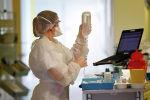 Врач в защитном костюме готовит капельницу в больнице с коронавирусом