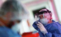 Врач надевает защитный экран в больнице с коронавирусом