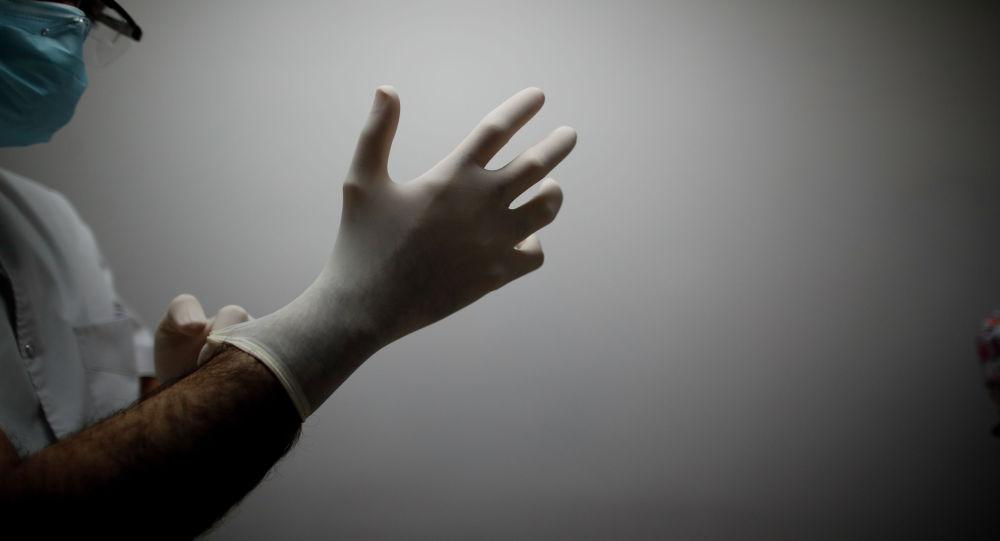 Врач в больнице с коронавирусом надевает перчатки