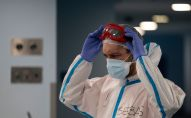 Врач поправляет защитные очки в больнице с коронавирусом