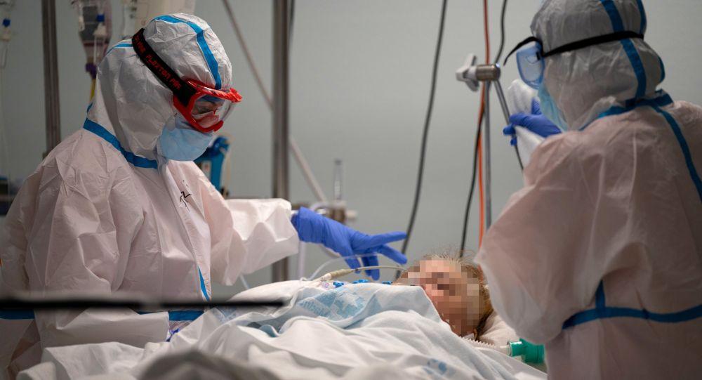 Врачи с пациентом в палате интенсивной терапии в больнице с коронавирусом