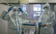 Врачи поправляют защитные костюмы в больнице с коронавирусом