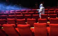 Сотрудник кинотеатра проводит дезинфекцию в зрительном зале