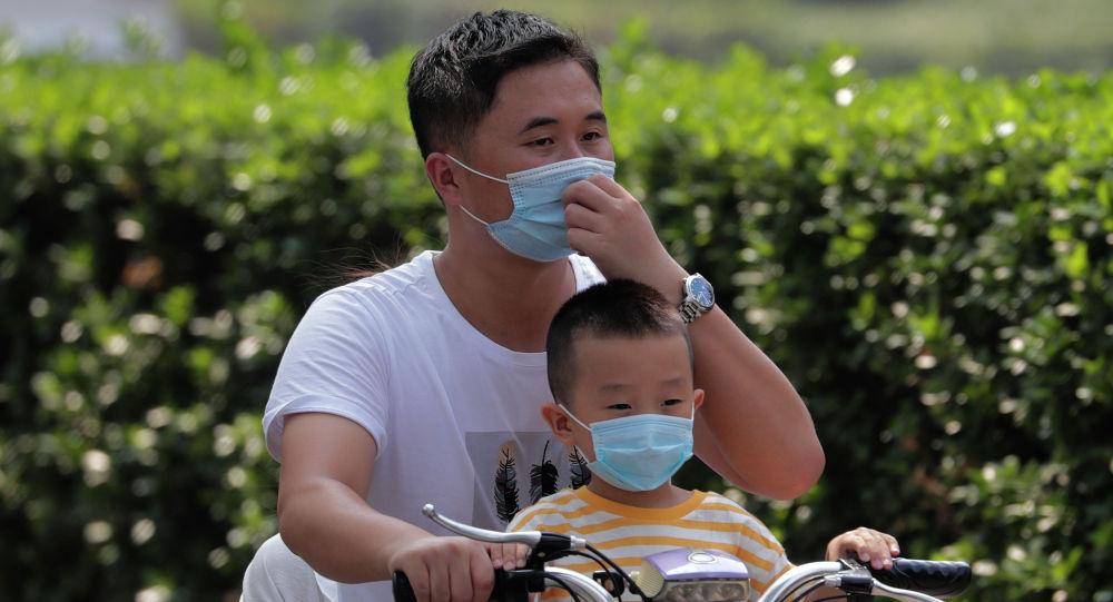 Мужчина и ребенок в масках на велосипеде