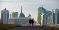 Мужчины идут по дороге на фоне Акорды, Байтерека и комплекса зданий госорганов