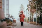 Женщина в маске идет по туманной улице