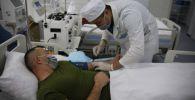 Врач обследует пациента в Алматинском военном госпитале
