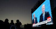 Люди смотрят прямую трансляцию дебатов Дональда Трампа и Джо Байдена на уличном экране