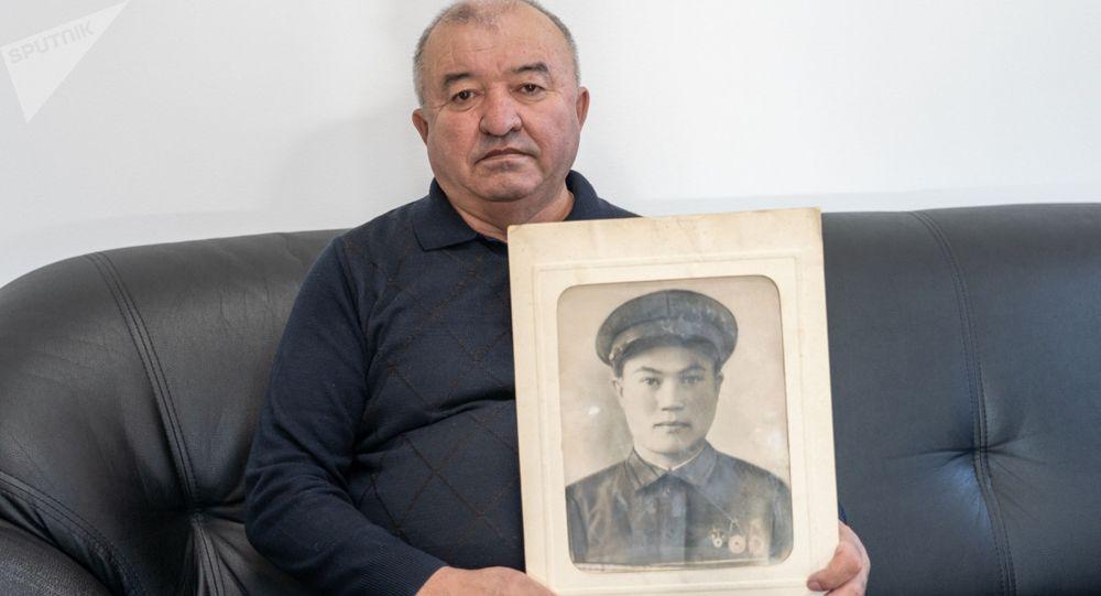 Внук найденного солдата Зимней войны Жумабек Мусин держит в руках портрет деда