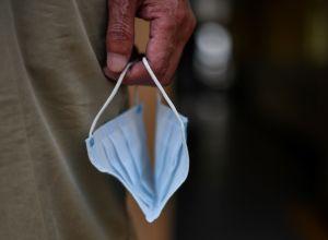 Пожилой человек держит держит маску в руке
