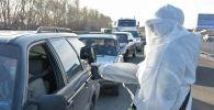 Врач измеряет температуру водителю автомобиля на блокпосте
