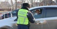 Полицейский проверяет документы у водителя автомобиля у блокпоста