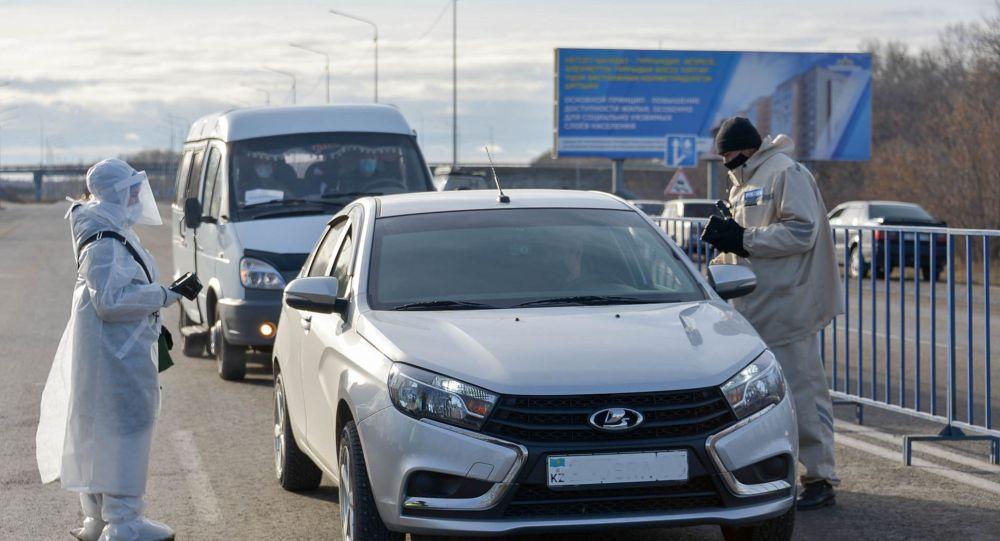 Врач и полицейский общаются с водителем автомобиля у блокпоста