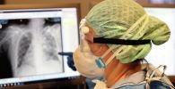 Медик в защитном костюме рассматривает рентгеновский снимок в больнице с коронавирусом