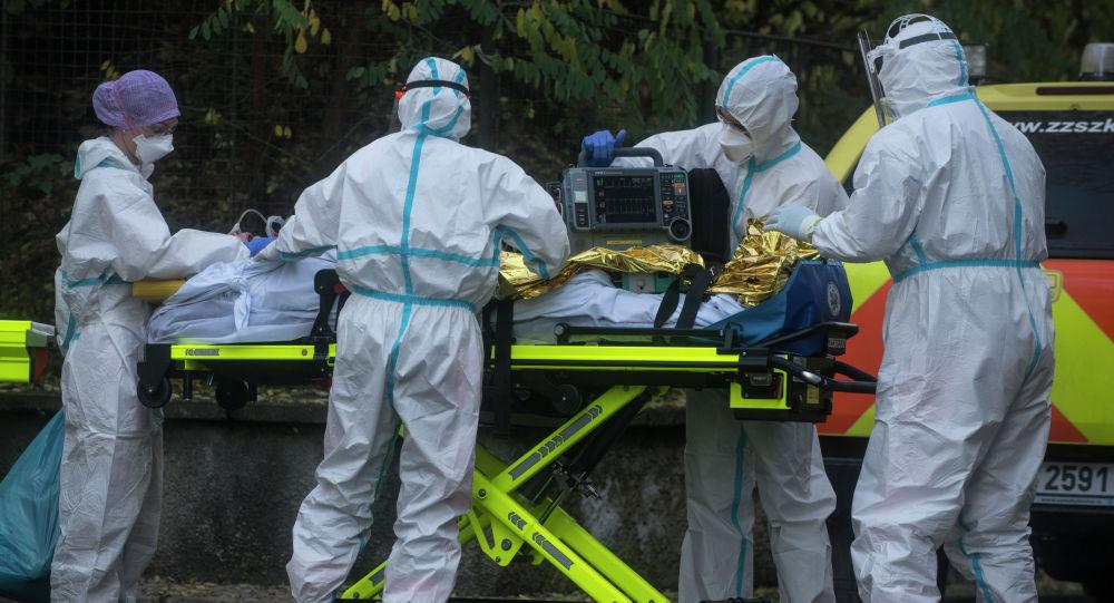 Врачи скорой помощи вывозят пациента с коронавирусом