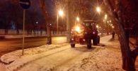 Сотрудники коммунальной службы чистят снег и посыпают тротуары