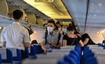 Пассажиры в защитных масках в салоне самолета, архивное фото