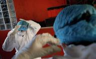 Медики надевают защитные костюмы перед началом смены в больнице с коронавирусом