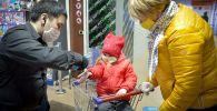 Сотрудник торгового центра измеряет температуру посетителям
