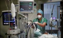 Медсестра в защитной маске следит за показателями приборов в палате интенсивной терапии в больнице с коронавирусом