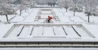 Мужчина на велосипеде во время снегопада в Софии, Болгария