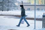 Мужчина в маске идет по заснеженной улице