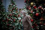 Пожилая женщина в маске идет мимо наряженных новогодних елок