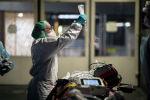 Медработник держит капельницу пациента, прибывшего в больницу с коронавирусом на скорой