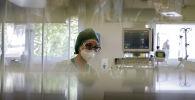 Медик наблюдает за пациентами в палате интенсивной терапии в больнице с коронавирусом